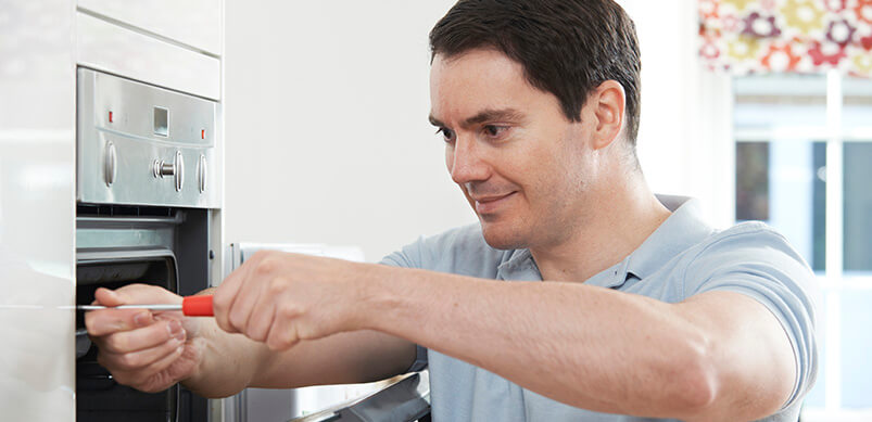 Hombre que arregla el horno en la cocina