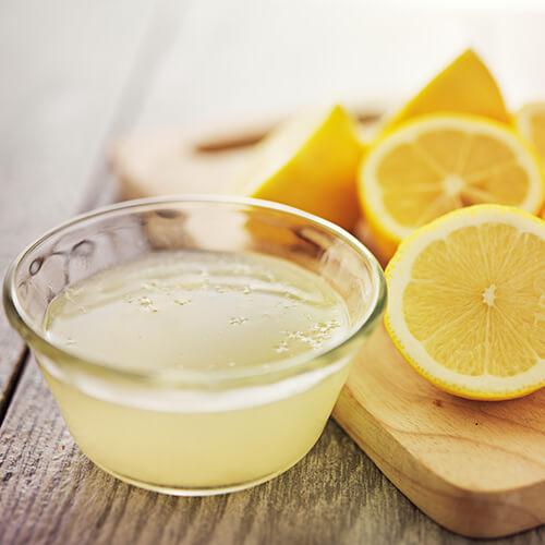 Jugo de limón en un recipiente con limones en el lado
