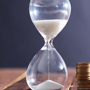 Reloj de arena con monedas en la mesa