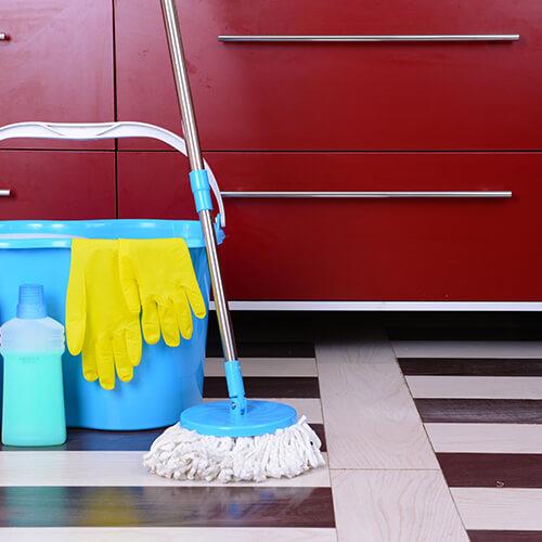 Espacio debajo del gabinete con productos de limpieza en el costado
