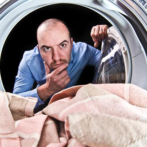 Hombre mirando a través de la máquina de lavar Mirando confundido
