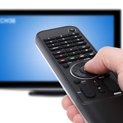 Control remoto de mano hacia la televisión