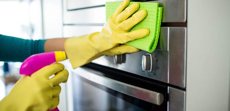 Manos en guantes de goma que limpian el frente del horno