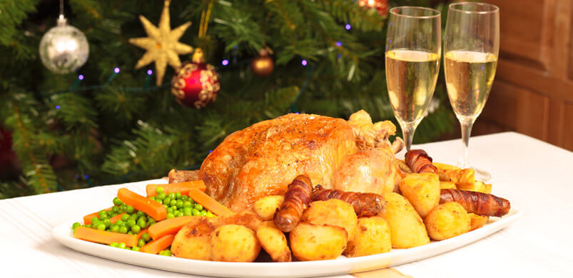 Cena de Navidad en la mesa con un árbol de Navidad detrás