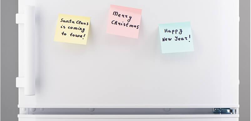 Puerta del refrigerador con notas adhesivas de Feliz Navidad