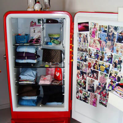 Nevera rota abierta con ropa doblada y fotos en la puerta