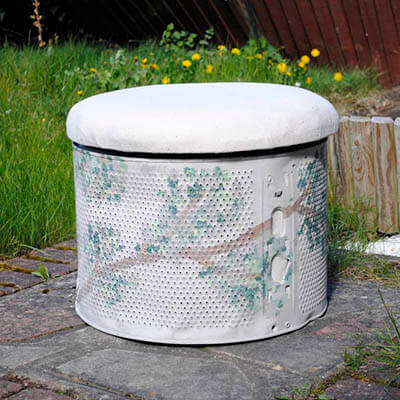 Reposapiés con cojín hecho de un tambor de la lavadora