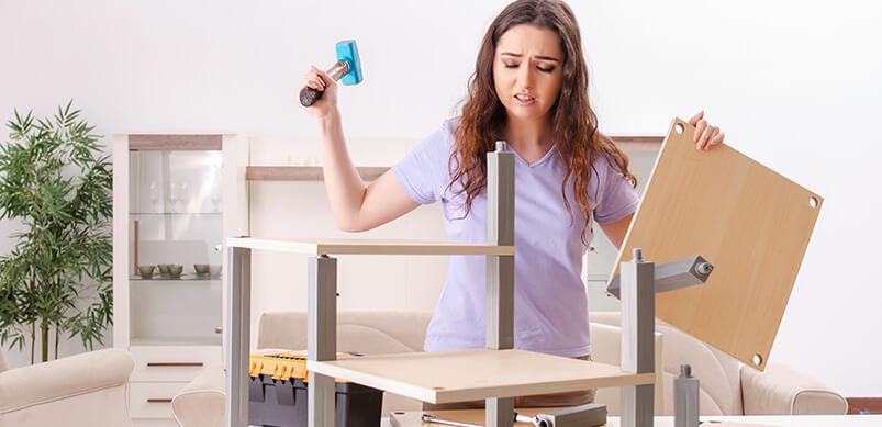 Mujer frustrada que ensambla muebles de paquete plano