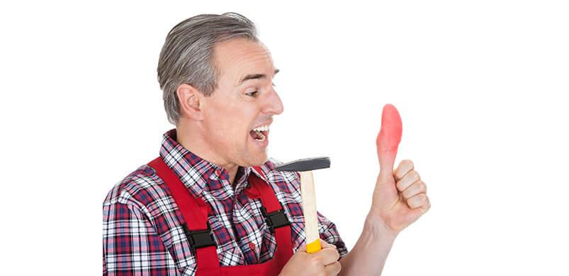 Hombre que sostiene un martillo con el pulgar lesionado