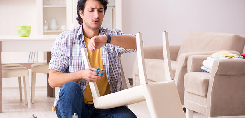 Hombre reparando muebles y comprobando el tiempo