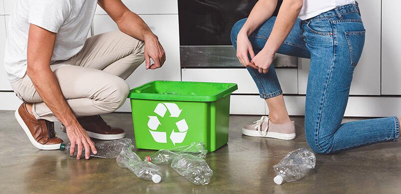 Pareja reciclando plástico en casa