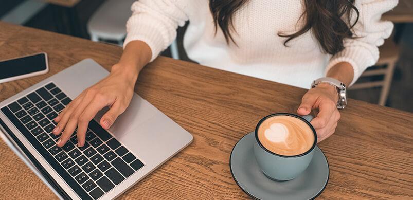 Mujer con laptop y taza de café en el escritorio